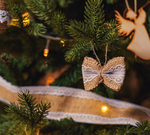 Burlap ribbon and ornaments on a Christmas tree-Restaurant Decorating Ideas for the Holiday Season