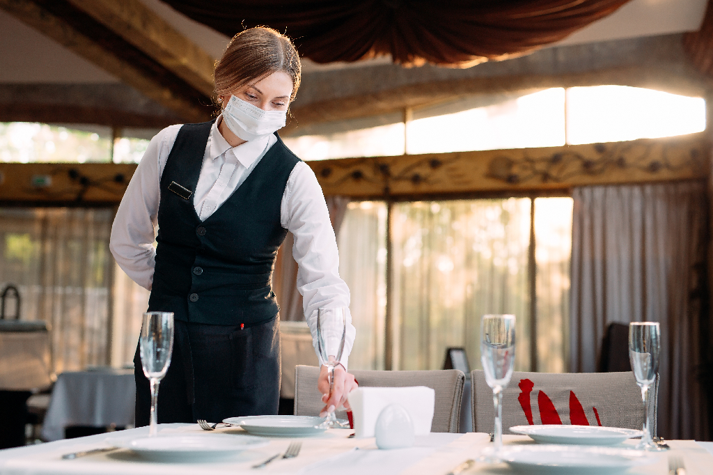 Waitstaff Setting Table with Face Mask On-Restaurant Safety: How to Keep Staff and Guests Safe Upon Reopening
