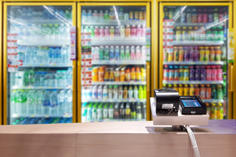Convenience Store Counter with Refrigerated Cold Case in Background - Convenience Store Delivery Ideas